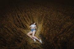 Женщина лежит в золотом поле пшеницы Стоковая Фотография RF