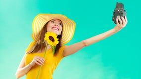 Женщина лета держит камеру солнцецвета старую стоковые фото