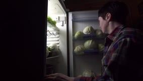 Женщина 40 лет на диете смотрит в холодильник на ноче сток-видео