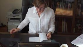 Женщина листая через дневник, раскрывает таблицу акции видеоматериалы