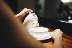 Женщина лить горячее питье стоковая фотография rf