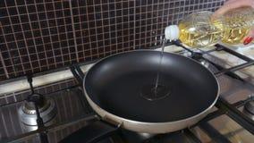 Женщина льет масло на сковороде видеоматериал