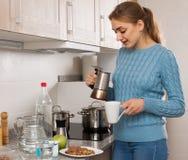 Женщина льет чашку кофе в кухне Стоковая Фотография