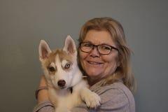 Женщина любовника собаки имея потеху с ее сиплым щенком стоковые фотографии rf