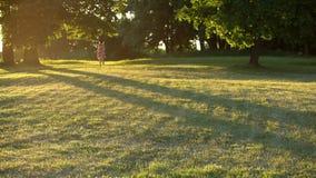 Женщина маленькой девочки в платье цветка красочном бежать через луг в парке сток-видео