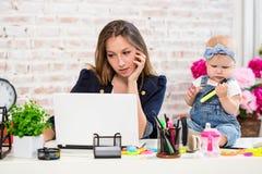 Женщина матери коммерсантки при дочь работая на компьютере Стоковое Изображение RF