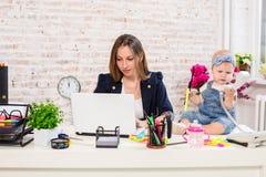 Женщина матери коммерсантки при дочь работая на компьютере Стоковое Фото