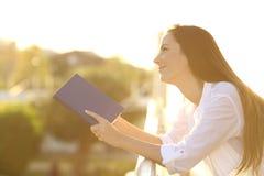 Женщина мечтая читающ книгу на заходе солнца Стоковое Изображение RF
