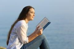 Женщина мечтая читающ книгу на пляже Стоковое Изображение RF