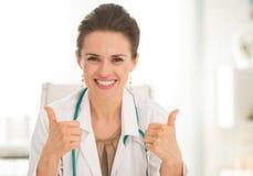 Женщина медицинского доктора показывая большие пальцы руки вверх Стоковое фото RF