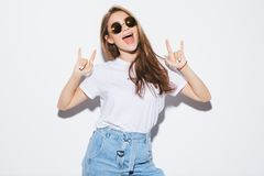 Женщина милой молодой моды чувственная представляя на белой предпосылке стены одетой в обмундировании джинсов стиля Стильный хипс стоковое изображение