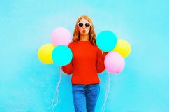 Женщина моды делает поцелуй воздуха с красочными воздушными шарами на сини стоковое фото