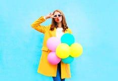 Женщина моды держит воздушные шары в желтом пальто на красочном стоковые изображения rf