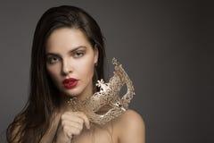 Женщина моды с длинными волосами и красной губной помадой с золотой маской стоковые фотографии rf