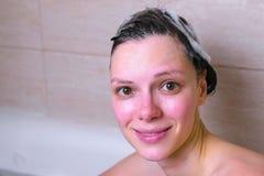 Женщина моет ее голову и волосы с шампунем в bathroom смотреть камеры стоковая фотография