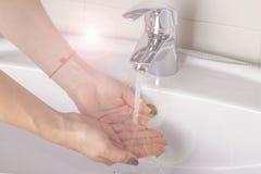 Женщина моет ее руки в раковине стоковая фотография rf