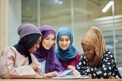 Женщина молодого дела пар мусульманская используя умный контакт телефона с партнером стоковое изображение