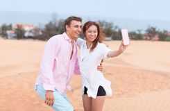 Женщина молодого человека идя в ландшафт песчанной дюны рук владением девушки и человека пар пустыни Стоковые Изображения RF