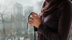 Женщина моля с розарием и деревянным крестом на предпосылке церков стоковые фото
