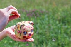 женщина монетки банка piggy кладя Стоковые Фотографии RF