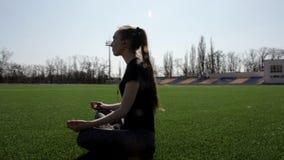 Женщина молодого привлекательного active подходящая делает йогу на траве огромного стадиона зеленой размышляя штилев наслаждающся видеоматериал