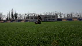 Женщина молодого привлекательного active подходящая сидя на траве огромного стадиона зеленой размышляя штилев наслаждающся теплым сток-видео