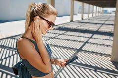 Женщина молодого фитнеса белокурая в музыке sportswear слушая Стоковые Фотографии RF