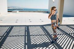 Женщина молодого фитнеса белокурая в музыке sportswear слушая Стоковые Изображения RF