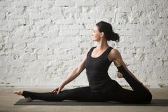 Женщина молодого yogi привлекательная в представлении бога обезьяны, предпосылке просторной квартиры Стоковое Фото