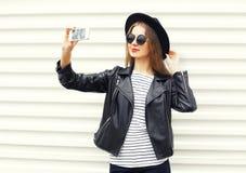 Женщина моды делает автопортрет на smartphone в черном стиле утеса над белизной Стоковые Изображения RF