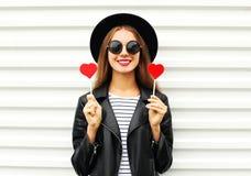 Женщина моды довольно сладостная молодая усмехаясь с красными губами держит куртку черной шляпы сердца леденца на палочке нося ко Стоковые Изображения RF