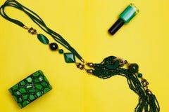 Женщина моды предметов первой необходимости возражает на аксессуарах желтой предпосылки женских: зеленый шарик серег браслета Пол Стоковые Изображения RF