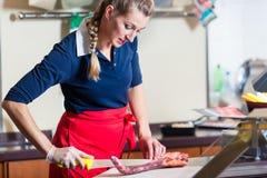 Женщина мясника режа часть мяса нервюры в ее магазине стоковые фотографии rf