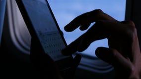 Женщина набирает сообщение на телефоне на самолете против окна иллюминатора в полете в вечер перста видеоматериал
