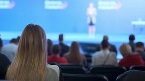 Женщина наблюдает семинар и слушает к диктору Обсудите концепцию экономического развития и новых технологий сток-видео