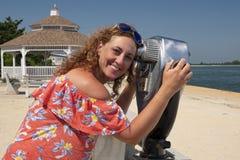 Женщина наблюдающ через бинокулярное эксплуатируемое монеткой Стоковые Фотографии RF