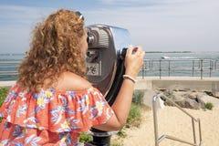 Женщина наблюдающ через бинокулярное эксплуатируемое монеткой Стоковое Изображение RF