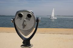 Женщина наблюдающ через бинокулярное эксплуатируемое монеткой Стоковые Фото