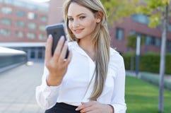 Женщина наблюдая в зеркале app мобильного телефона Стоковые Фото