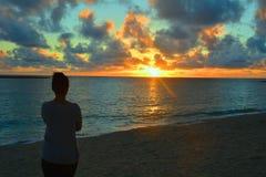 Женщина наблюдая заход солнца стоковая фотография rf