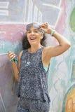 Женщина над 50 с граффити smartphone огораживает предпосылку Стоковые Фотографии RF
