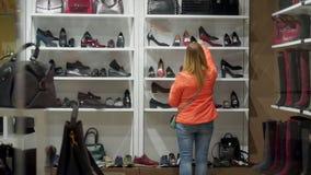 Женщина назад в обувном магазине, выбирает его ботинки и ботинки акции видеоматериалы