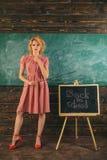 Женщина назад к школе Милая женщина в винтажном платье с указателем на классн классном класса Прелестный и гений стоковые фотографии rf