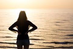 Женщина наслаждаясь заходом солнца на пляже Стоковое Фото