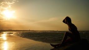 Женщина наслаждаясь красивым заходом солнца на пляже Стоковое фото RF