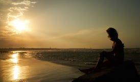 Женщина наслаждаясь красивым заходом солнца на пляже Стоковое Фото