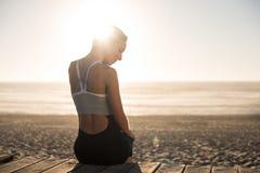 Женщина наслаждаясь красивым заходом солнца на пляже Стоковые Фото