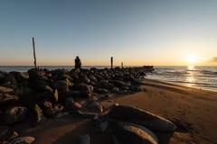 Женщина наслаждаясь холодным заходом солнца весны на пляже валуна око стоковое фото rf