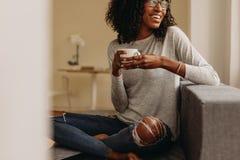 Женщина наслаждаясь чашкой кофе сидя дома стоковое фото