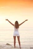 Женщина наслаждается заходом солнца над морем стоковые изображения
